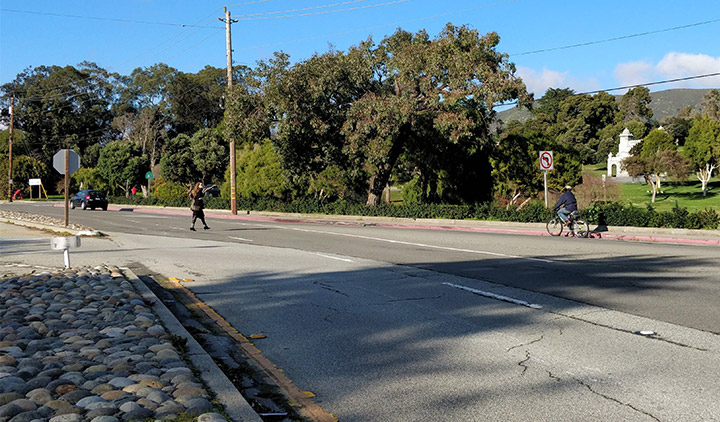 Woman walking across El Camino Real and man bicycles along El Camino Real in the Town of Colma.