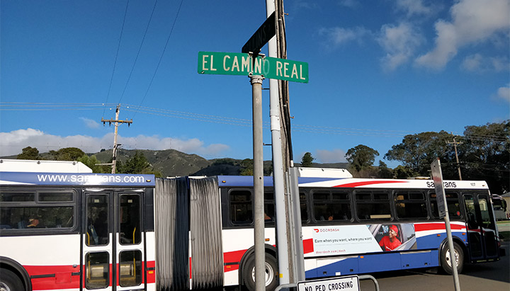 A green El Camino Real street sign with a SamTrans bus passing by in the background