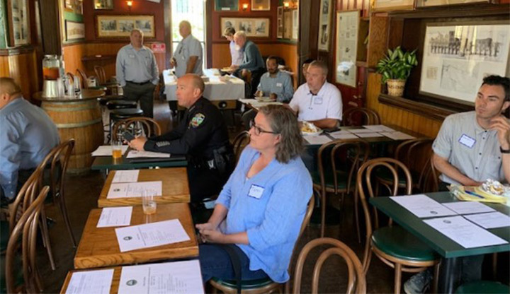 Men and women gather at a restaurant in the Town of Colma for a community outreach meeting.