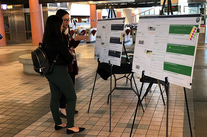two women look at project display boards at a BART station.
